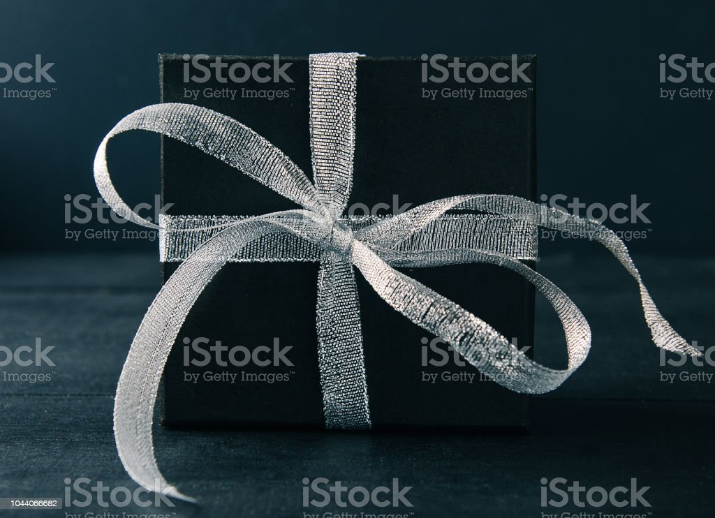 Black gift box with silver ribbon bow on black background. Tonned...