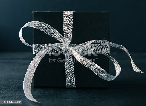 istock Black gift box with silver ribbon bow on black background. Tonned photo. 1044066682