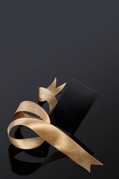 black gift card with a gold ribbon - award ribbon stock photos and pictures