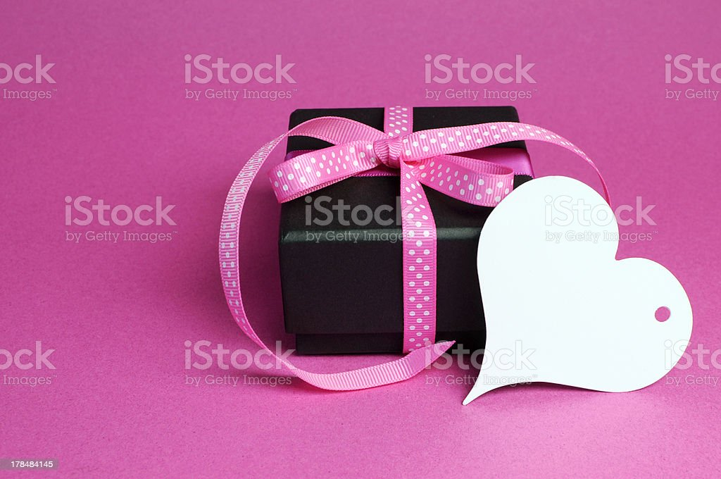 Black gift with pink ribbon and white heart tag. royalty-free stock photo