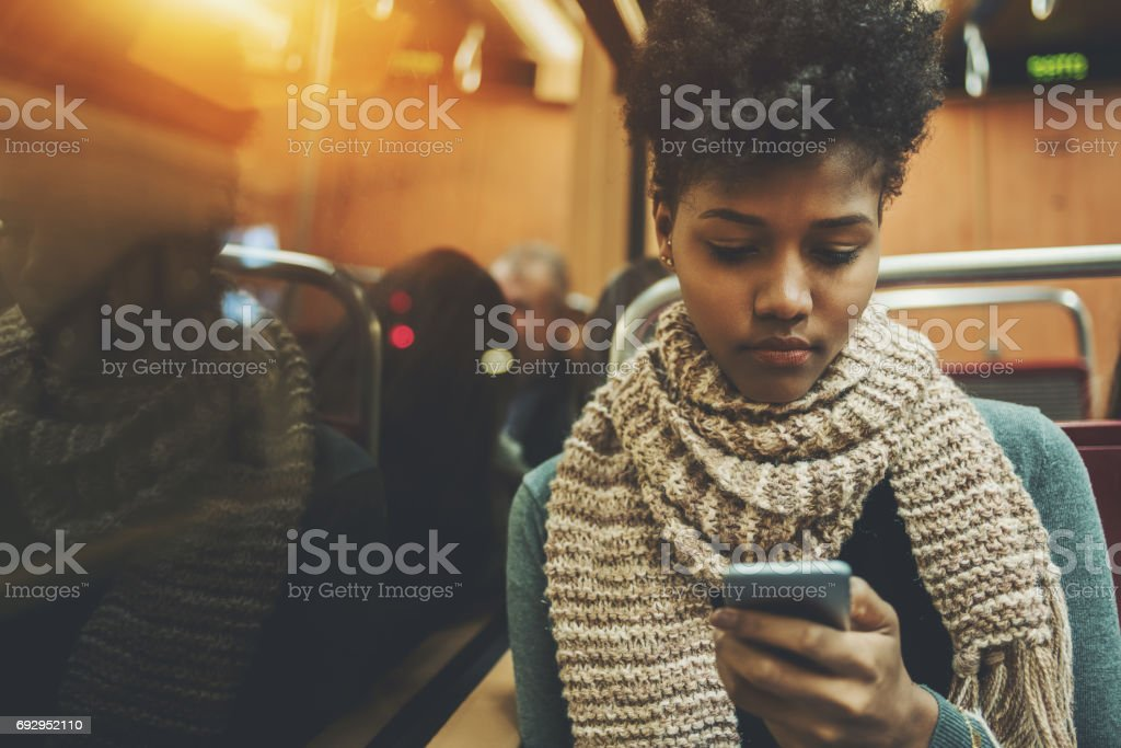 Black gilr in coach of train with smartphone stock photo
