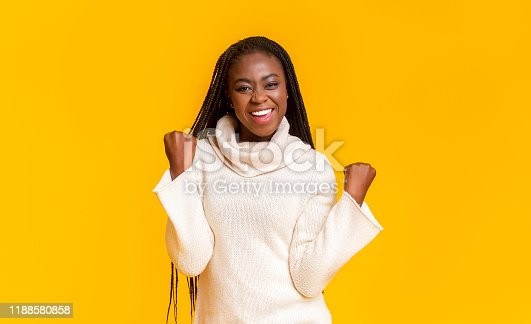 657442382istockphoto Black girl celebrating success, clenching fists over yellow background 1188580858