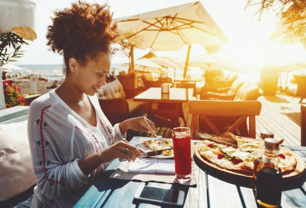 Fille noire manger pizza á café de rue - Photo