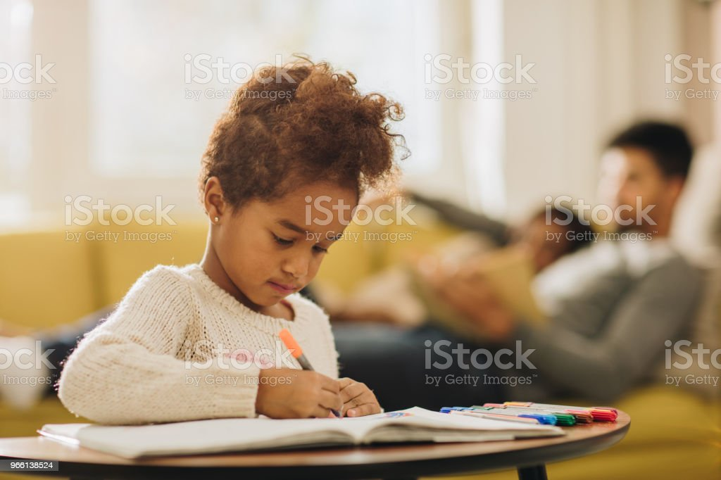 Zwarte meisje genieten tijdens het tekenen lagen in het notaboek thuis. - Royalty-free Afrikaanse etniciteit Stockfoto