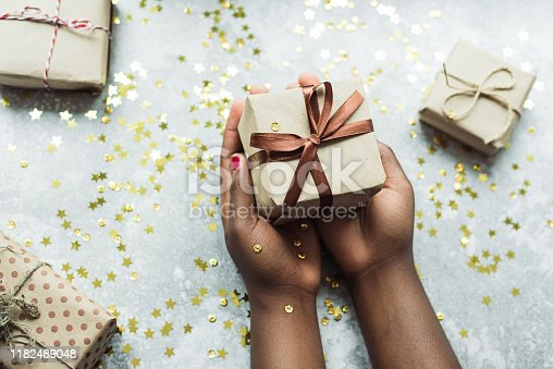 Black girl gives a gift made with her own hands. Hands holding a craft gift with a brown ribbon on a gray background with a few small gifts. Flat lay.