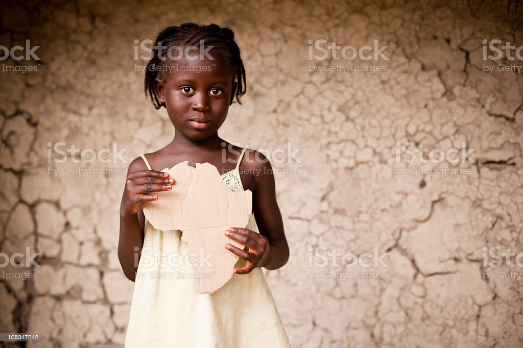 Black girl holding a piece of cardboard shaped like Africa royalty-free stock photo