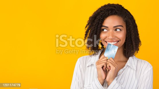 istock Black girl holding credit card thinking about market 1201174779