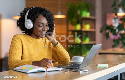 Happy black girl in wireless headphones studying online, using laptop and taking notes, cafe interior, copy space