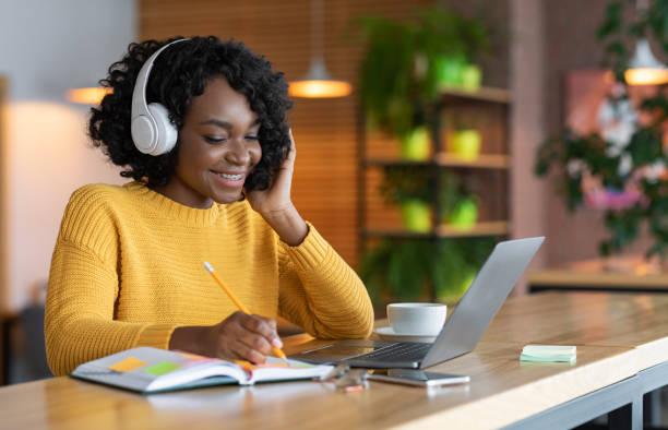 坐在耳機裡的黑人女孩在網上學習,在咖啡館使用筆記本電腦 - 成年人 個照片及圖片檔