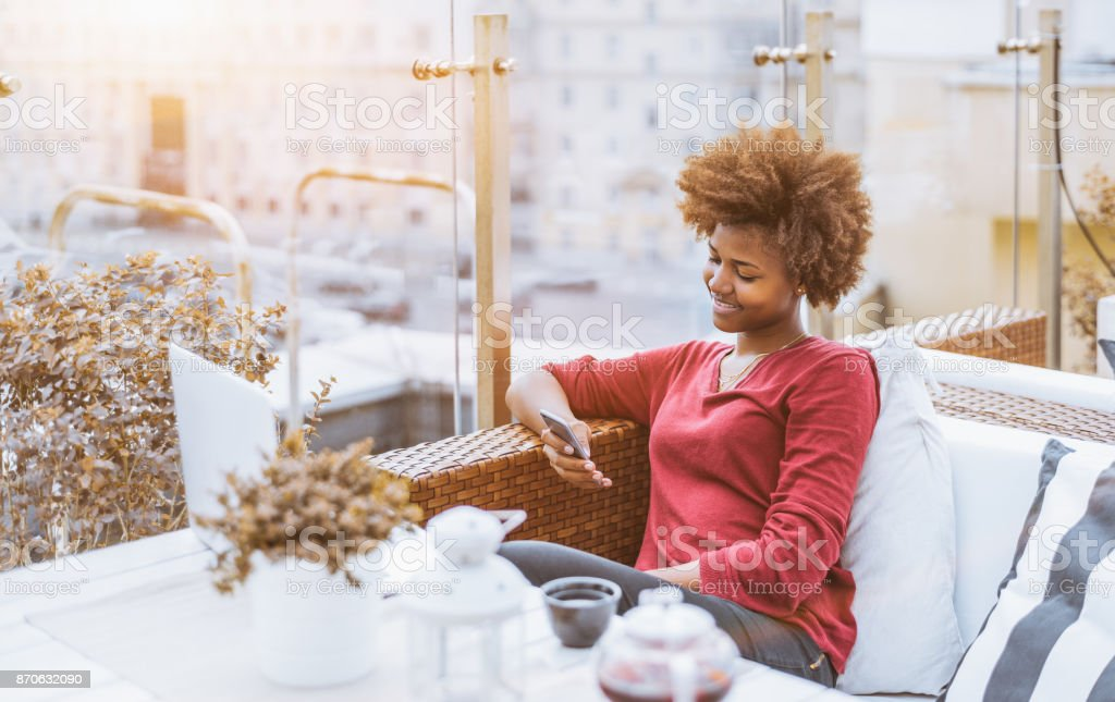 Black girl in luxury street bar with smarphone and laptop stock photo