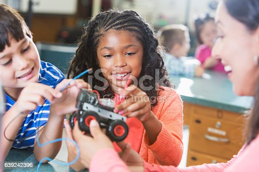An 8 year old mixed race black and Hispanic girl in a science lab with other students and a teacher learning about robotis. She and a boy are working on a model vehicle, attaching wires.