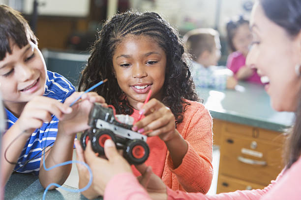 Black girl in science class learning robotics - foto stock