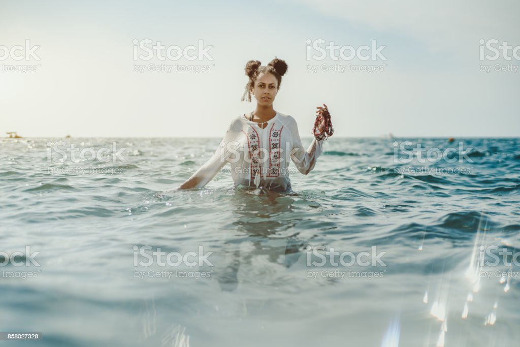 Black girl in teal water stock photo