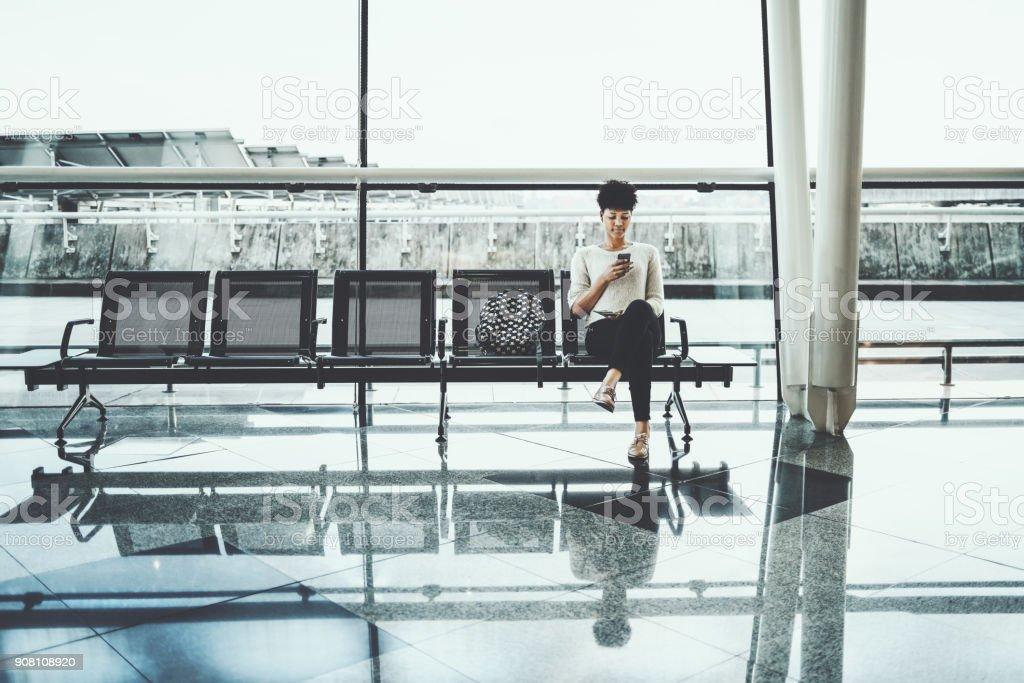 Schwarzes Mädchen im Wartesaal des Bahnhofs mit smartphone – Foto