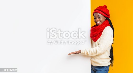 1168002879 istock photo Black girl in winter set directing to blank board 1184189879