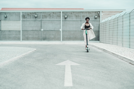 istock Black girl is riding an e-scooter 1174770045