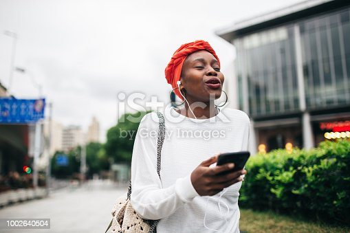 One woman, standing on the street in city, using smart phone, listening music on headphones.