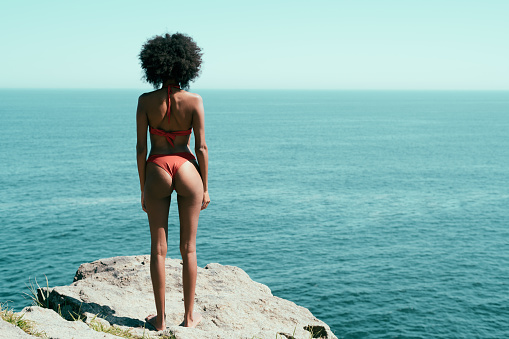 View from behind of a svelte young African-American woman with a curly black afro hair, standing on a cliff of a tropical resort in a swimsuit on a hot summer day and observing seascape and a horizon
