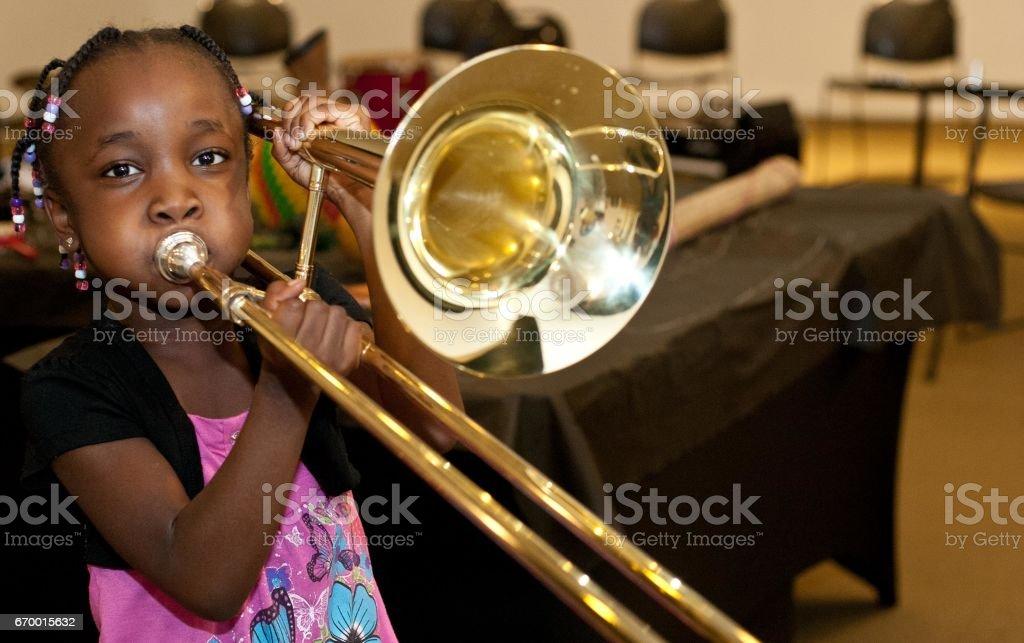 Black girl playing a trombone stock photo