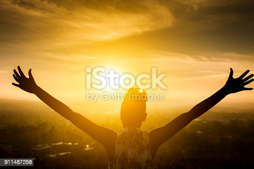 Silhouette of a beautiful black girl raising her arms over the valley as the sun sets