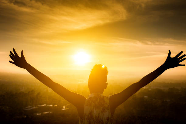 black girl raising arms over valley in sunset - praise and worship stock photos and pictures