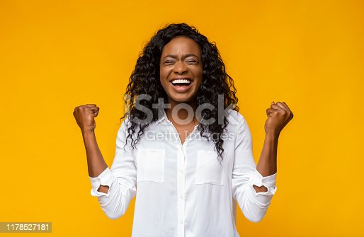 657442382istockphoto Black girl shouting and raising clenched fists in the air 1178527181