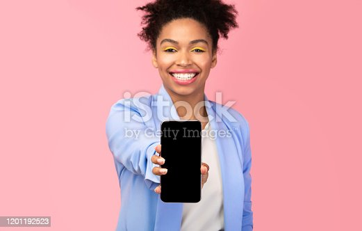 1084491176 istock photo Black girl showing blank cell phone screen at studio 1201192523