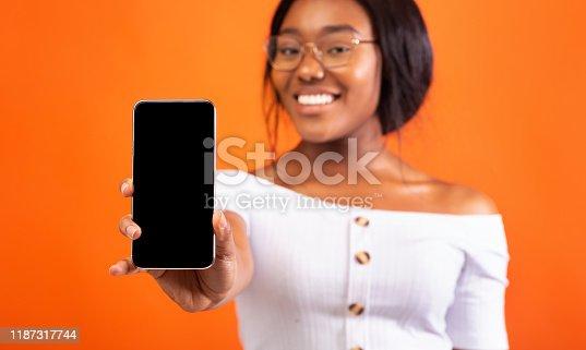1132512759istockphoto Black Girl Showing Phone Empty Screen Standing, Orange Background, Mockup 1187317744