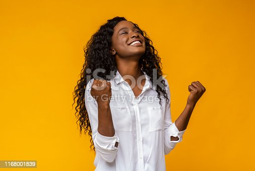 Emotional african american woman smiling and raising clenched fists in the air, feeling excited, yellow studio background