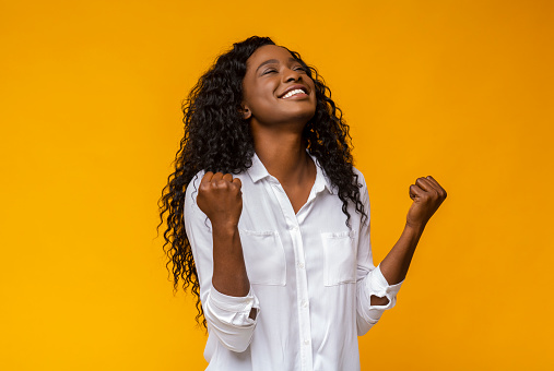 Black Girl Smiling And Raising Clenched Fists In The Air Stock Photo - Download Image Now