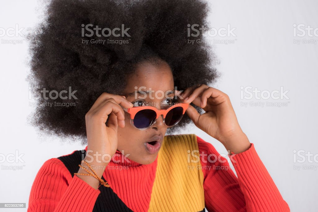 Black girl surpised at what she sees.She adjusts sunglasses. stock photo