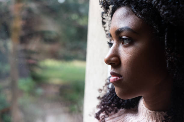 Black girl watching out of the window stock photo