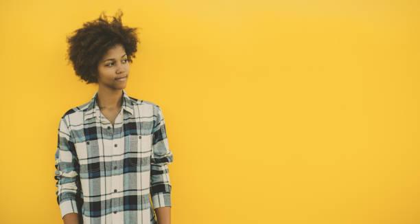 chica negra con espacio de copia sobre fondo amarillo - sólido fotografías e imágenes de stock