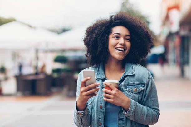 schwarze mädchen mit telefon und kaffee im freien in der stadt - outdoor handy stock-fotos und bilder