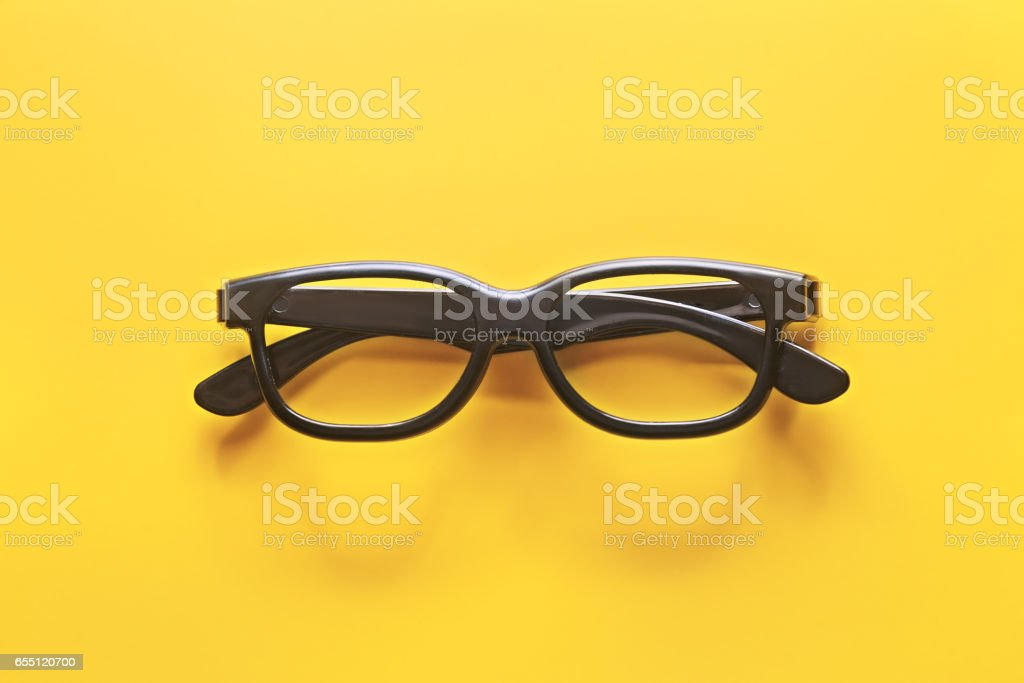 Black glasses on a yellow background stock photo