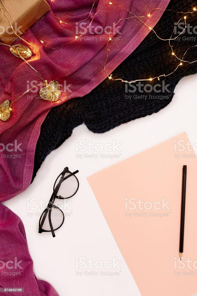 De óculos escuros, rosa papel com metas de ano novo. Cachecol e Natal luzes no fundo branco - foto de acervo