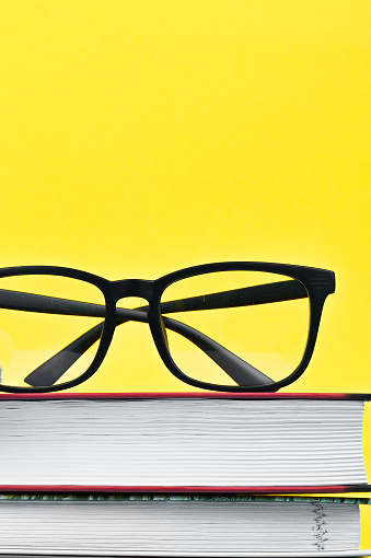 black glasses with books on a yellow background. High quality photo