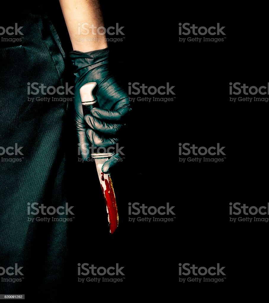 Black Glove and Bloody Knife Black gloved hand holding a bloody knife. Aggression Stock Photo