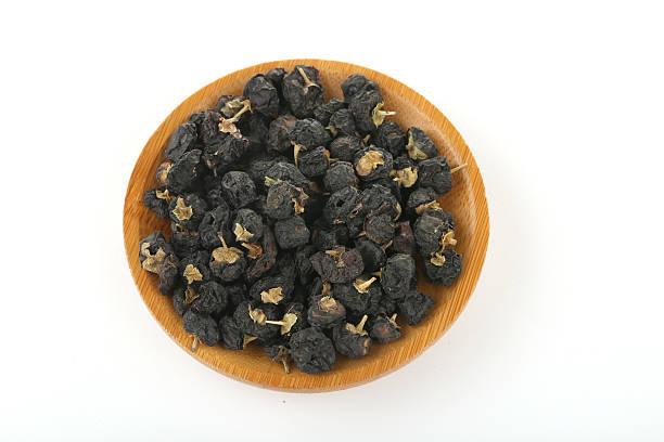 Black goji wolfberry in a wooden bowl ストックフォト