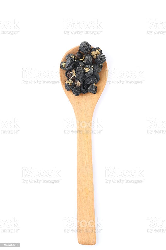 Black goji wolfberry in a wooden spoon on the white ストックフォト