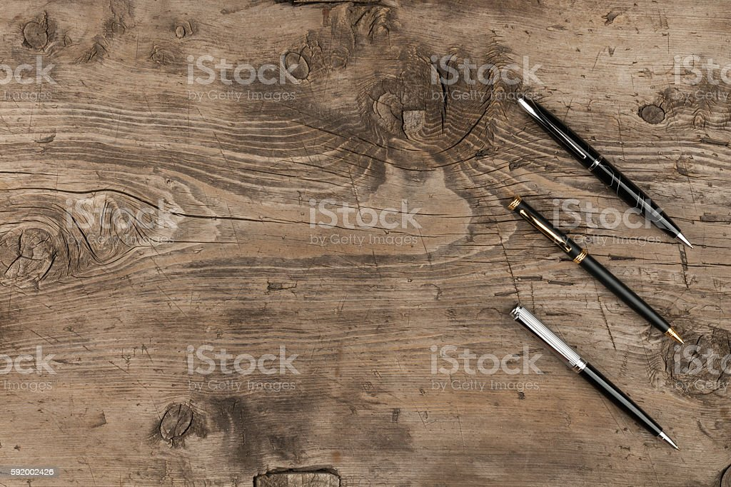 Black, gold and silver pens on a wooden texture - foto de stock