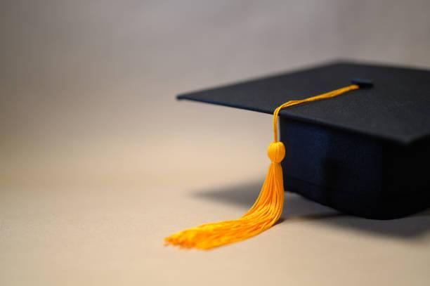 gorra de graduación negra colocada sobre papel marrón - graduación fotografías e imágenes de stock