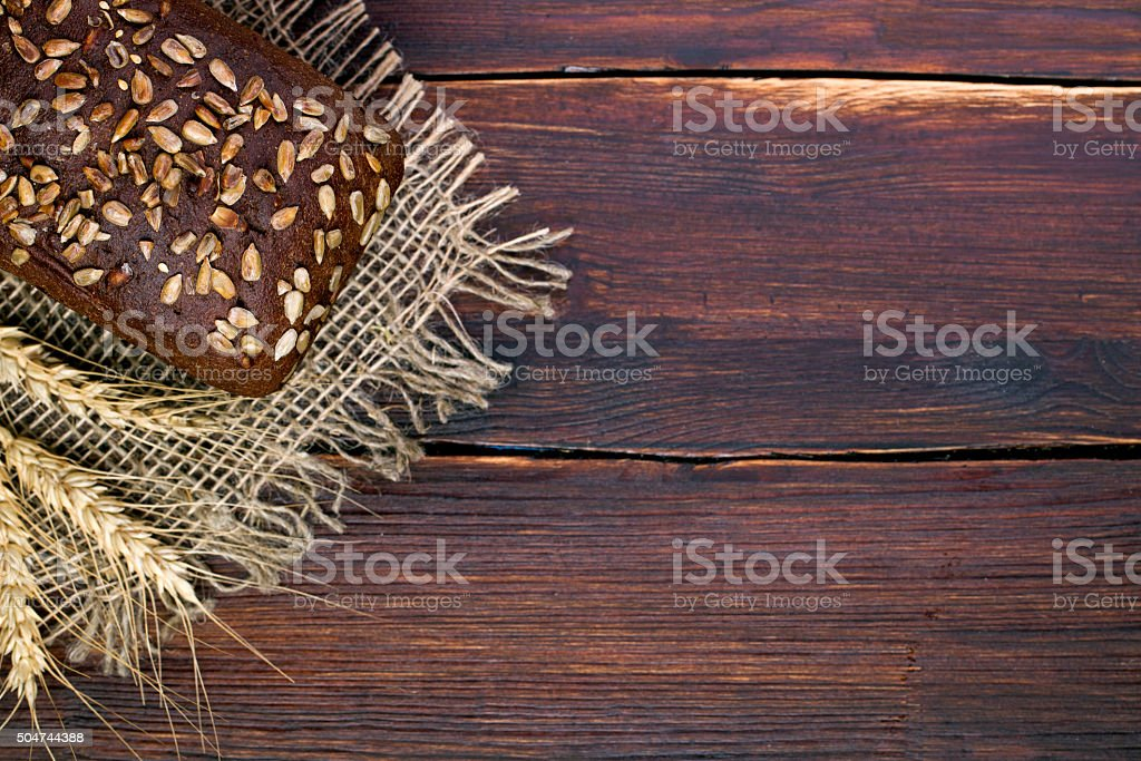 Black grain bread and wheat on the wooden stock photo