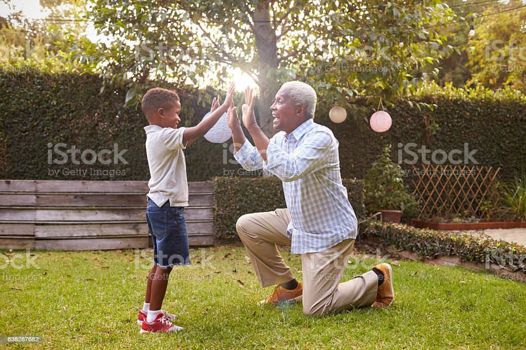 Black grandfather plays with grandson in garden, full length stock photo