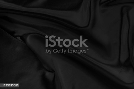 682260934 istock photo Black gray satin dark fabric texture luxurious shiny that is abstract silk cloth background with patterns soft waves blur beautiful. 1223293558