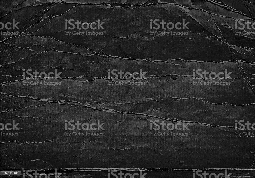 Black grunge background from old creased cardboard paper texture stock photo