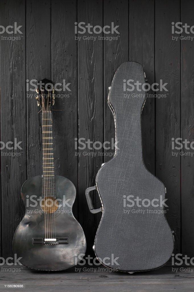 black guitar on a black wooden background