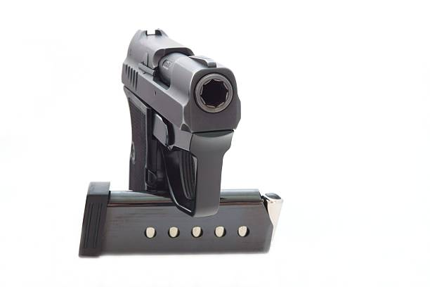 Black gun from metal The black gun from metal and the holder with cartridges costs vertically on a white background deathly stock pictures, royalty-free photos & images