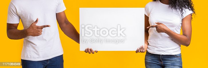 1168002879 istock photo Black guy and girl holding white blank card 1171084349
