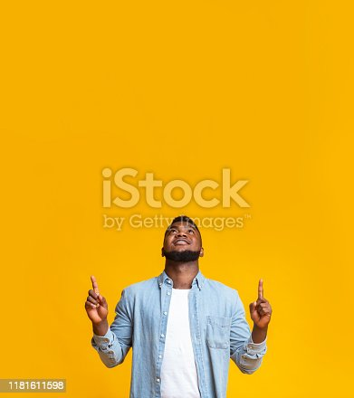 1165538246 istock photo Black guy pointing upwards at copy space on yellow background 1181611598